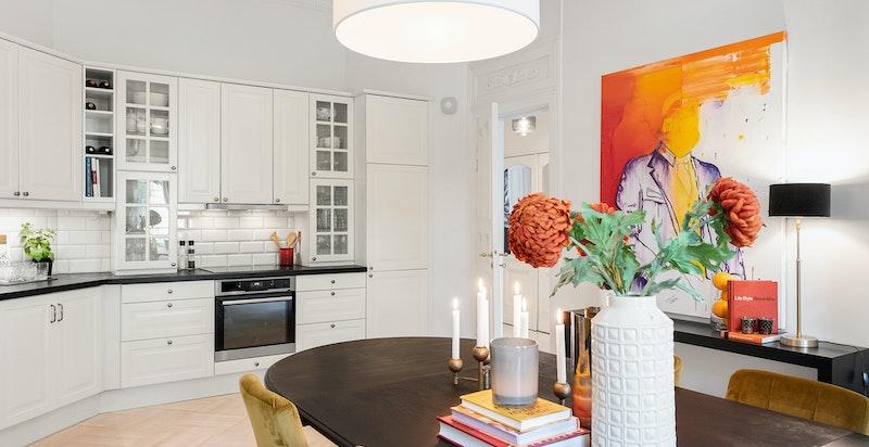koselig spisestue med åpen kjøkkenløsning med spisebord ved store vinduer og peis også her
