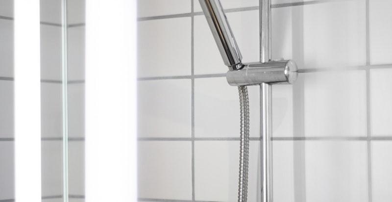 Badet inneholder vegghengt wc, dusjhjørne, servant og opplegg til vaskemaskin/tørketrommel.
