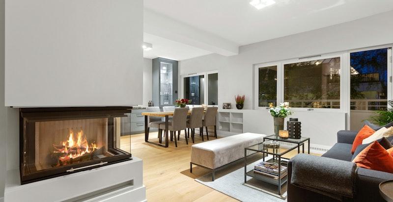 Stuen har en tidsriktig og moderne peis med hev/senk dør.
