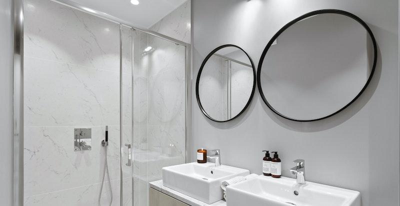 Stilfullt og moderne bad med dobbelt servant og dusjhjørne, samt opplegg for vaskemaskin/tørketrommel.