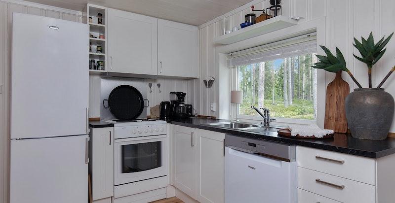 Kjøkken med kjøleskap, oppvaskmaskin og komfyr