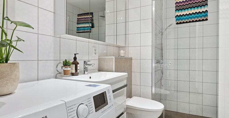 Delikat flislagt bad med regnfallsdusj og vegghengt toalett.
