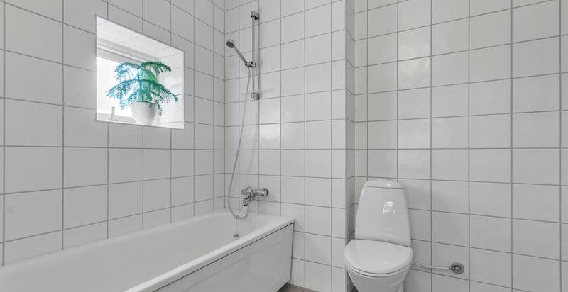Innredet med servant i diverse innredning, dusj i badekar, klosett. Opplegg for vaskemaskin og tørketrommel