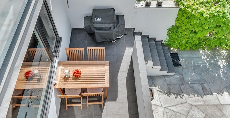 Trapp ned fra terrassen leder ned til det private uteområdet/hagedelen på 65 m²
