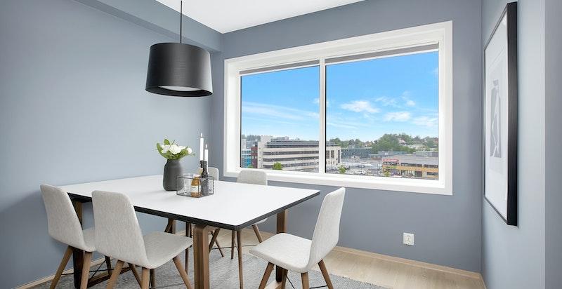 Det er god plass til både sofa -og spisegruppe. Store vindusflater gir rikelig med naturlig lys