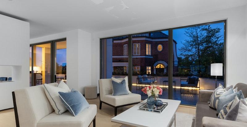 Romslig stue med utgang til terrasse. Kveldsstemning.