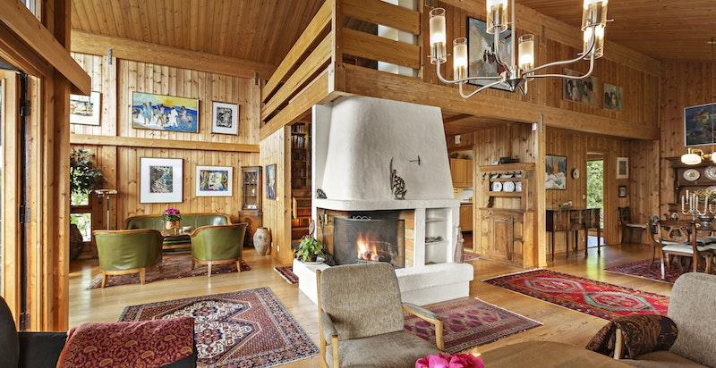 Stort oppholdsrom med stue med peis, spisestue og plass til flere salonger