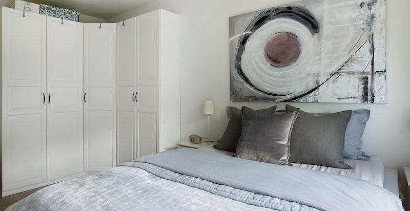 Snekkertilpasset romslig garderobeskap i hjørnet av hovedsoverommet