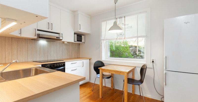 Kjøkken med hvitevarer og hyggelig spiseplass