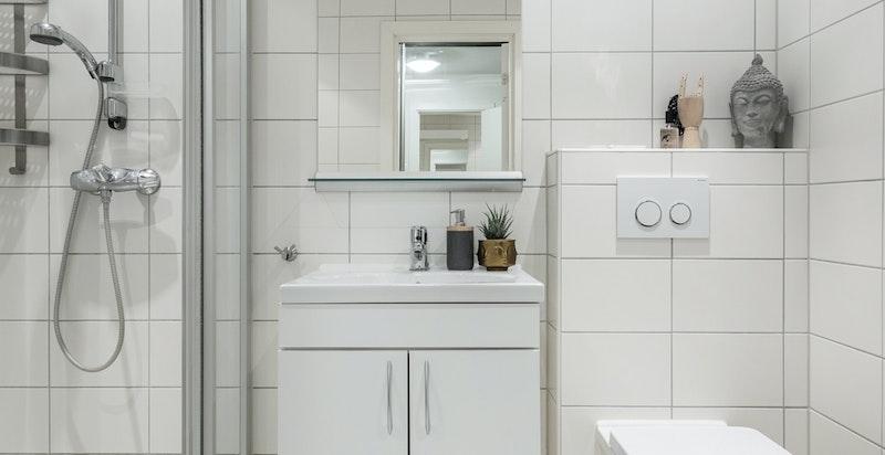 Delikat og romslig baderom med dusjhørne, servant for oppbevaring og vegghengt toalett.