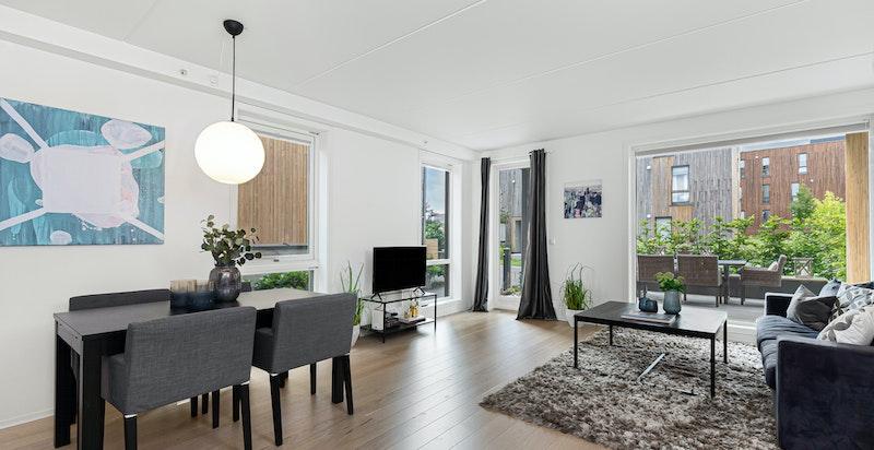 Romslig stue med store vindusløsninger som gir mye lys