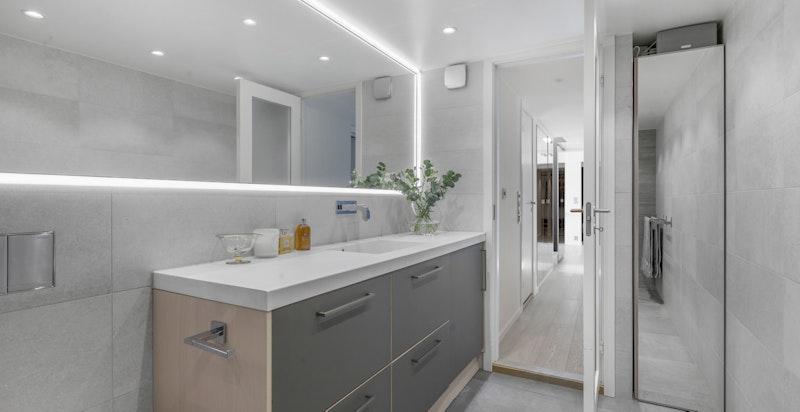 Badet har skapinnredning fra HTH (med integrert kombi vask/tørk), vegghengt klosett og flott speil med LED-belysning rundt, samt varmekabler i gulv.