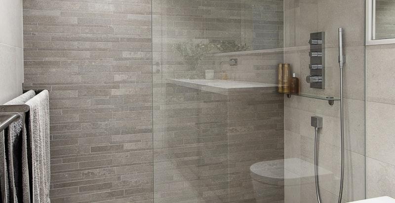 Stor dusjsone i elegant design fra Vola og Axor, inkludert regnfallsdusj i himling, vegg- og hånddusj. Lekre fliser på vegger og gulv, inkludert flisbelagt sluk fra Purus.