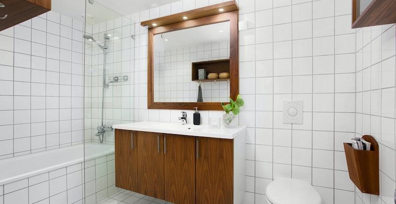 Flislagt bad med dusj i badekar tilhørede hovedsoverommet
