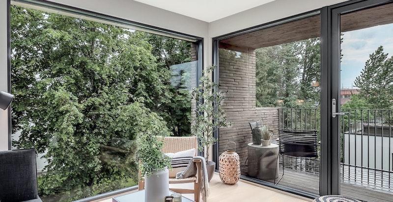 Stue med store vindusflater og utgang til sydvendt balkong. Grønt og hyggelig utsyn.