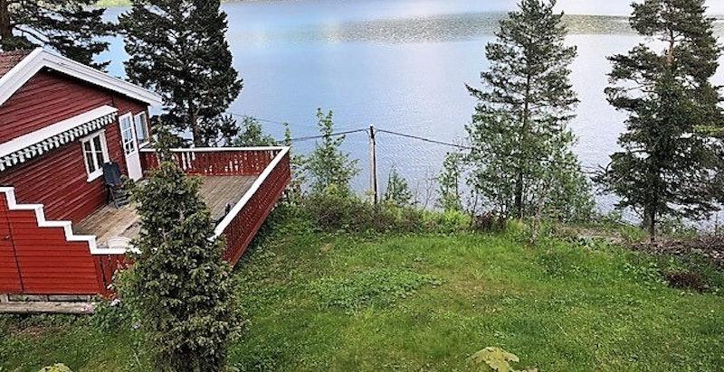 Hyggelig flat hage ut fra terrassen og skrånende naturtomt bakover