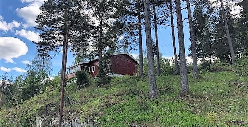 Tatt nedenfra Modumveien, hytta ligger høyt og fritt over