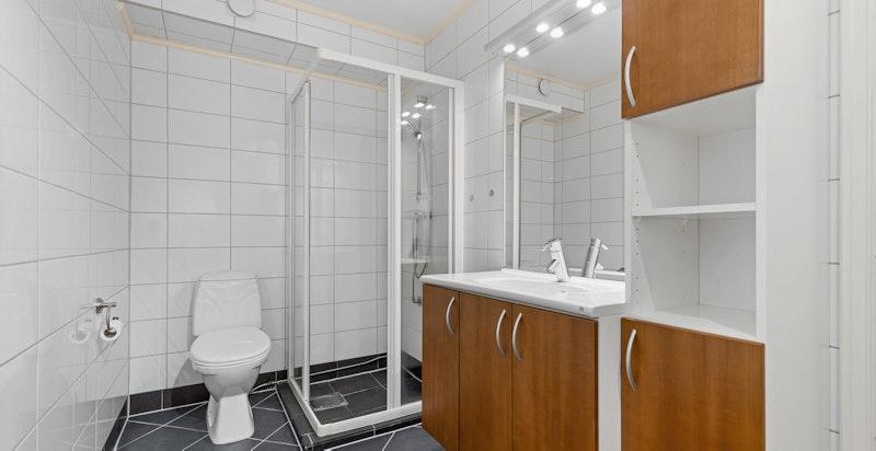 Leiligheten har et pent og romslig flislagt bad med varmekabler og opplegg til vaskemaskin/tørketrommel.