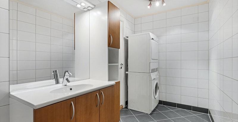 Badet er innredet med servant i skap, ettgreps blandebatteri, speil over servant med belysning og høyskap.
