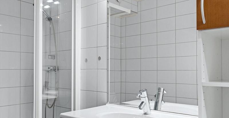 Frittstående toalett og dusj med glassvegger.