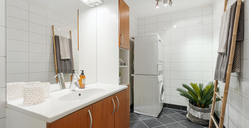 Pent og romslig flislagt bad med varmekabler og opplegg til vaskemaskin/tørketrommel.