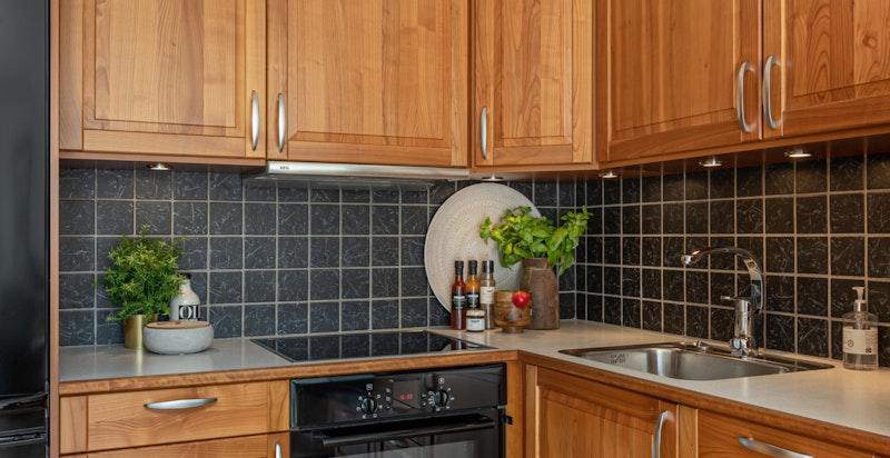 Hvitevarerne inkluderer komfyr, platetopp, oppvaskmaskin og nisje for kjøleskap.