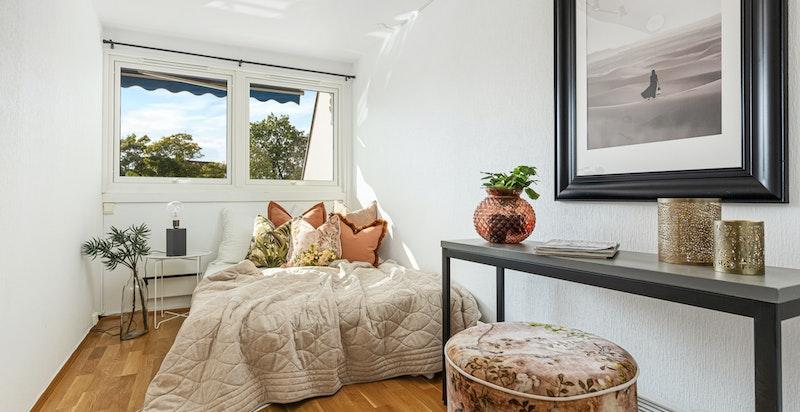 Romslig soverom med plass til dobbeltseng og tilhørende møblement.