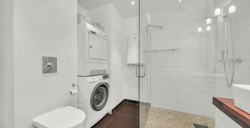 Romslig dusjsone i hjørne med glassvegg/-dør, regnfallsdusj og hånddusj. Vegghengt klosett med skjult sisterne. Medfølgende vegghengt stellebord fra ByBo Design. Opplegg for vaskemaskin og tørketrommel