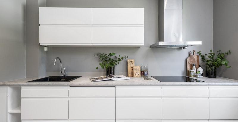 Helintegrerte hvitevarer som inkluderer veggplassert stekeovn, induksjonstopp, oppvaskmaskin og kjøl/frys.