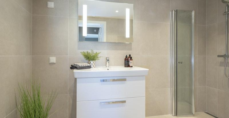 Badet er utstyrt baderomsinnredning med heldekkende servantplate, blandebatteri og speil med integrert belysning.