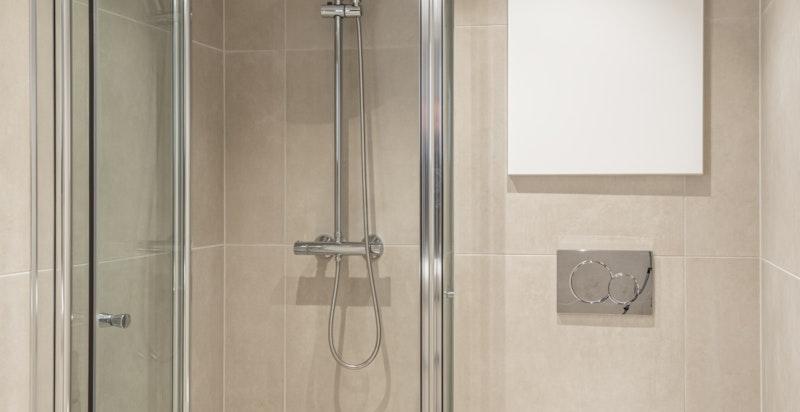 Vegghengt toalett og dusjnisje med glassdør (foldedør). Opplegg til vaskemaskin og tørketrommel.