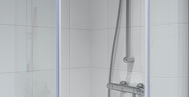 Dusjhjørne med innfellbare dusjvegger i herdet glass. Opplegg for vaskemaskin.