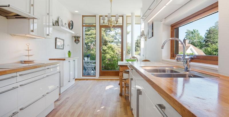 Kjøkken med spiseplass, noe fjordutsikt og utgang til terrasse/hage med morgensol