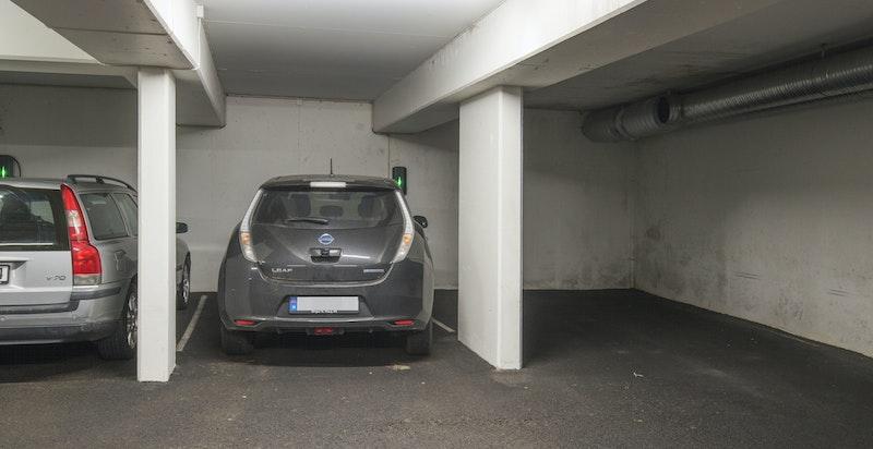 To garasjeplasser i underjordisk anlegg - det er montert medfølgende ladestasjon for el-/hybridbil