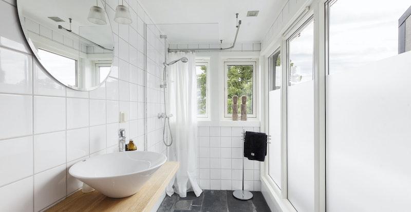 Bad - skålservant på heltre benk. Store vindusflater.