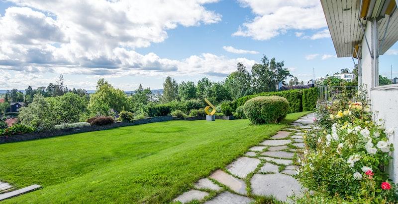 Skiferlagt gangvei rundt store deler av boligen - flott parkmessig opparbeidet hage