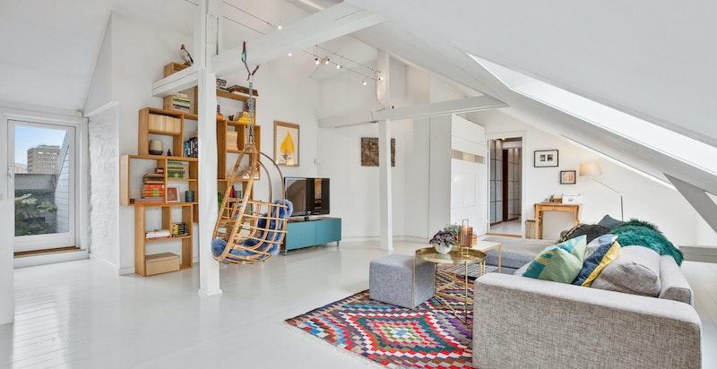 Stuen er svært luftig og lys med herlige sjarmerende og synlige takbjelker.