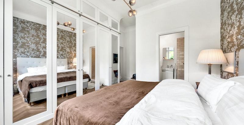 Snekkerbygde garderobeskap i heltre eik med speildetaljer