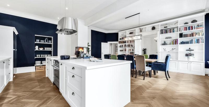 Lekkert snekkerbygget kjøkken med profilerte fronter med stålhåndtak, corian benkeplater med kum med blandebatteri, kjøkkenøy med skuffer og medfølgende bred Smeg komfyr med platetopp