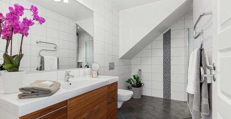 Hovedbadet i 2.etg. er utstyrt med servantskap, innfliset speil, vegghengt toalett og dusjnisje med foldedør i glass