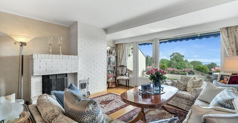 Stuen med peis og store vindusflater