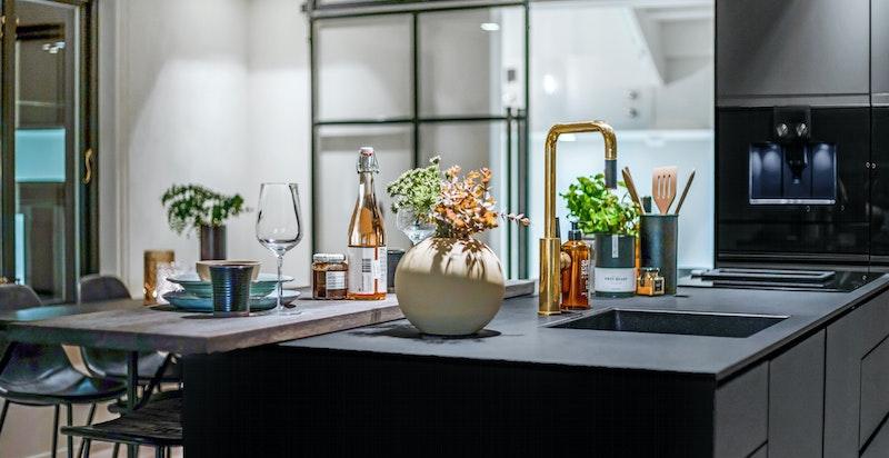 Detaljbilde kjøkken. Kjøkkenøy med moderne barløsning. Smijernsdør.