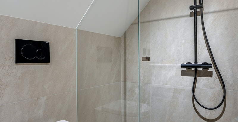 Pent flislagt bad i 2. etasje med servant med underskuffer, vegghengt klosett og dusj.