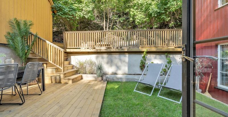 Både fra gangen og kjøkkenet/stuen er det utgang til en skjermet og idyllisk hage som går over to nivåer.