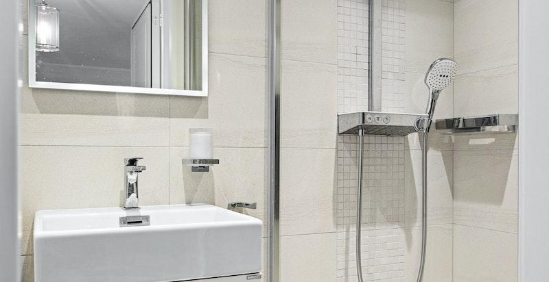 Delikat flislagt baderom med dusj, toalett og servant med skap.
