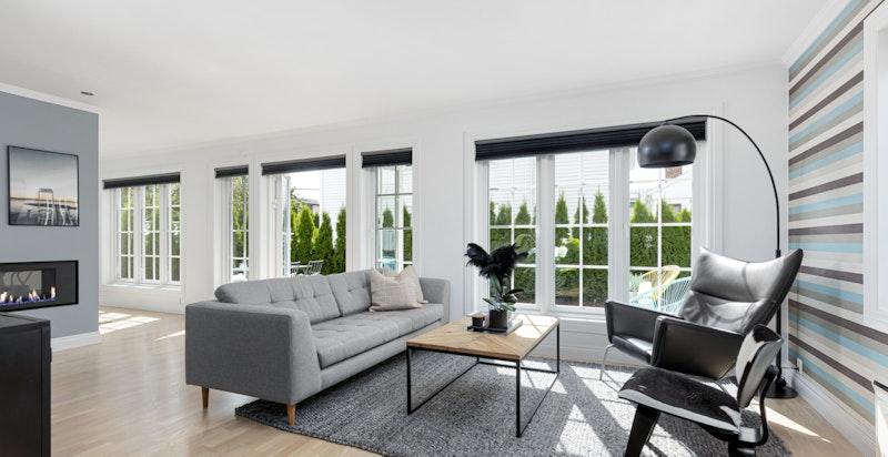 Åpen hjørnestue med store vindusflater og utgang til terrasse