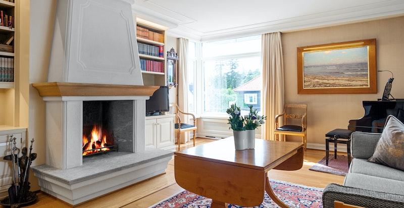 Stue med peis, plassbygget bokhylle og vakre gulv.