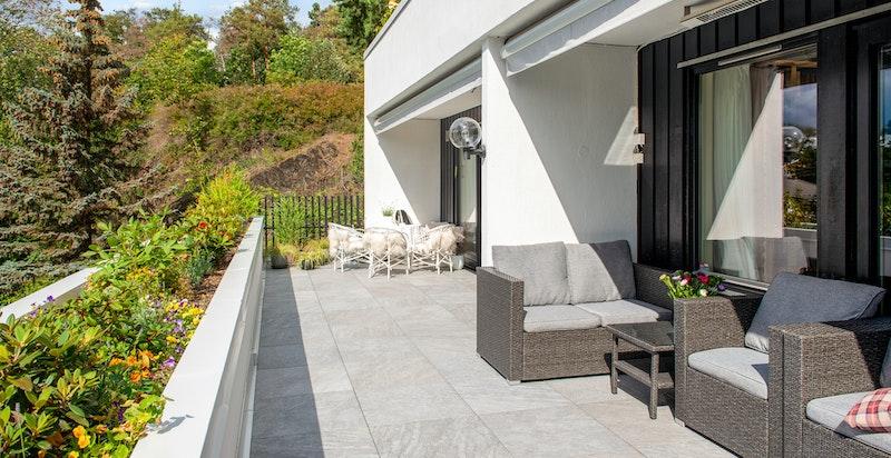 Stor, solrik terrasse mot vest med utgang fra stue og soverom