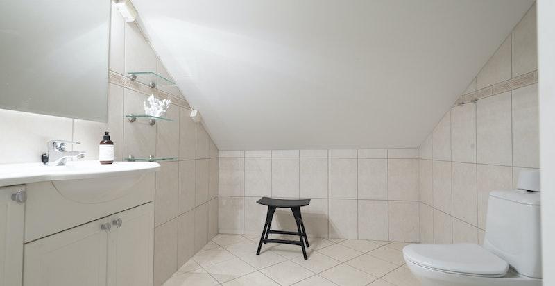 Praktisk baderom fra 2004 med dusj, toalett og servant.