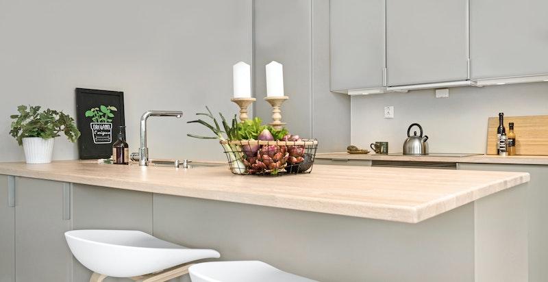 Bred kjøkkenøy med spiseplass.